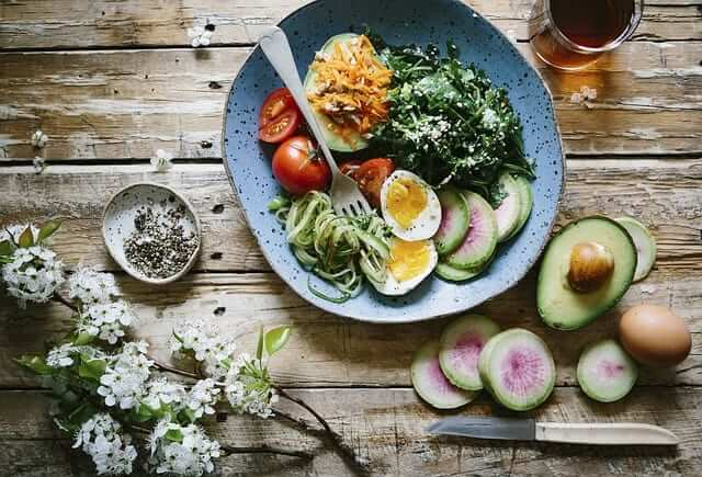 healthy bowl with veggies, avocados and eggs