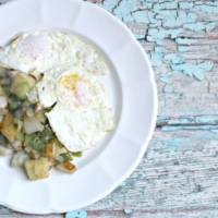 two eggs over medium with stewed potatoes and vegetables on a white plate, all on a blue painted wooden table