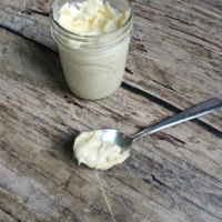 jar of mayonnaise next to a spoon topped with mayonnaise, resting on dark natural wood