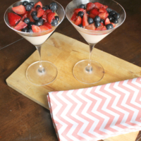 two cocktails glasses filled with yogurt, blueberries and strawberries on a wooden cutting board, with an accompanying pink and white napkin, all over a dark brown wooden table