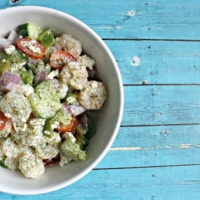 chicken and cucumber salad with feta in a white bowl on a blue painted wooden table