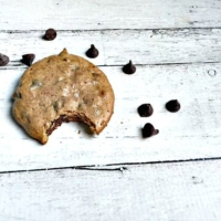cookie with one bite removed, surrounded by chocolate chips all on a white painted wooden table