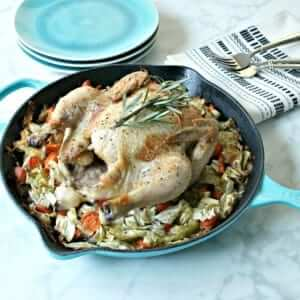 close overhead shot of a roasted chicken on a bed of vegetables in a blue cast iron skillet, next to cutlery and teal stone flatware