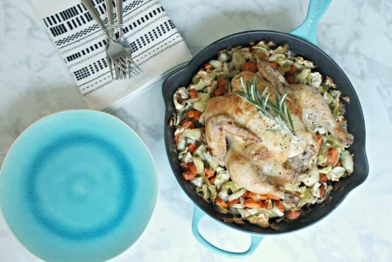 overhead shot of a roasted chicken on a bed of vegetables in a blue cast iron skillet, next to cutlery and teal stone flatware