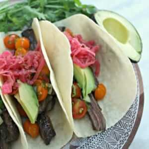 close shot of three steak tacos with two pitted avocado halfs and sprigs of cilantro on a patterned plate upon a white marble countertop