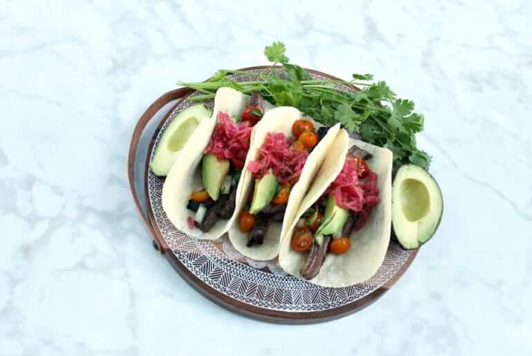 three steak tacos with two pitted avocado halfs and sprigs of cilantro on a patterned plate upon a white marble countertop