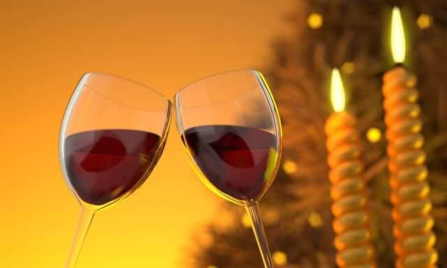two glasses of red wine with Christmas lights in the background