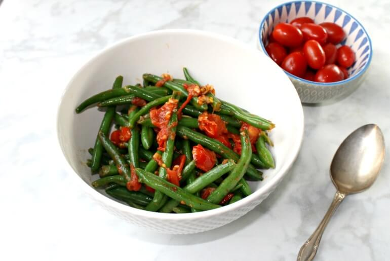 overhead shot of green beans with tomatoes and garlic, with a spoon and a small bowl full of cherry tomatoes on a white marble countertop
