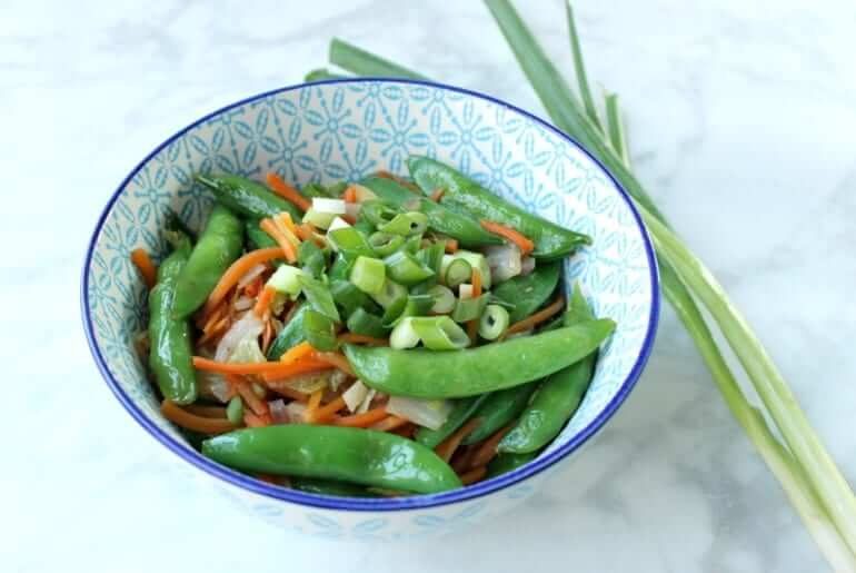 close shot of a patterned blue bowl containing edamame, green onions, carrots, and other vegetables with two sprigs of green onion