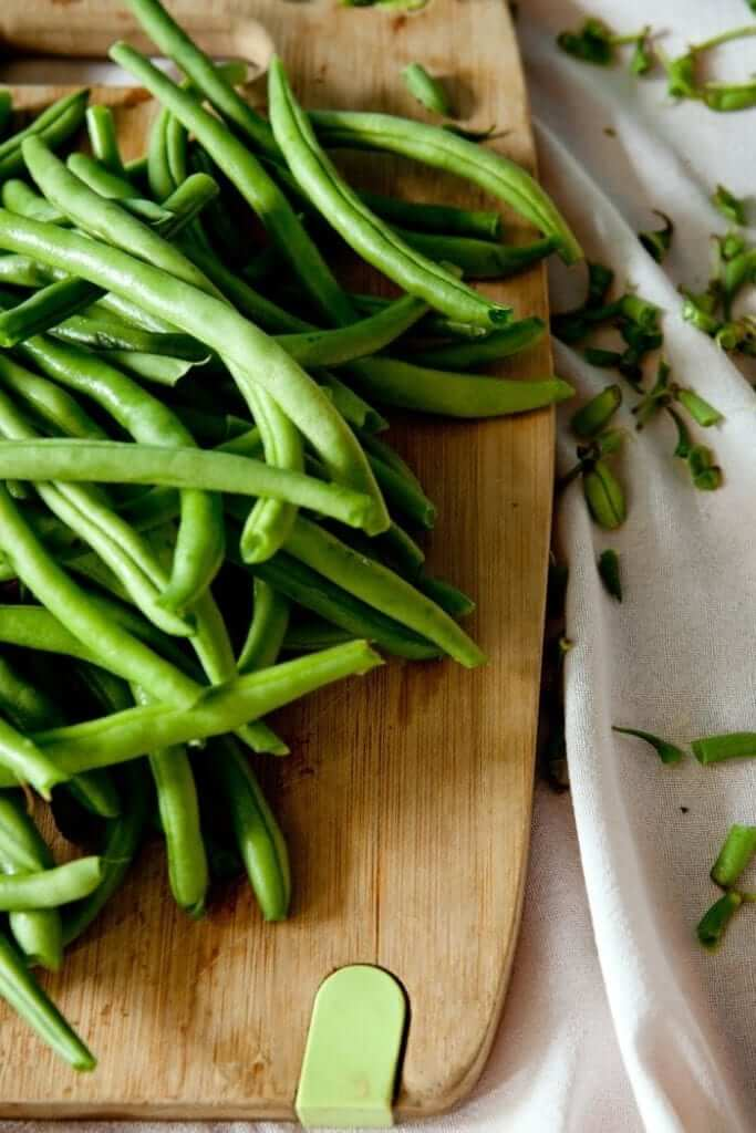 green beans being prepared on a chopping board for making a healthy paleo garlic beans side dish