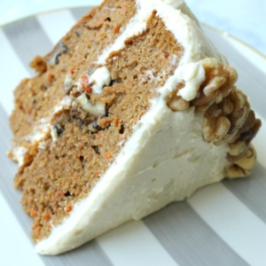slice of carrot cake with white frosting and walnut detailing on a striped plate