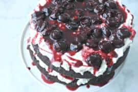 chocolate layered cake on a white plate with cherries and white frosting between layers