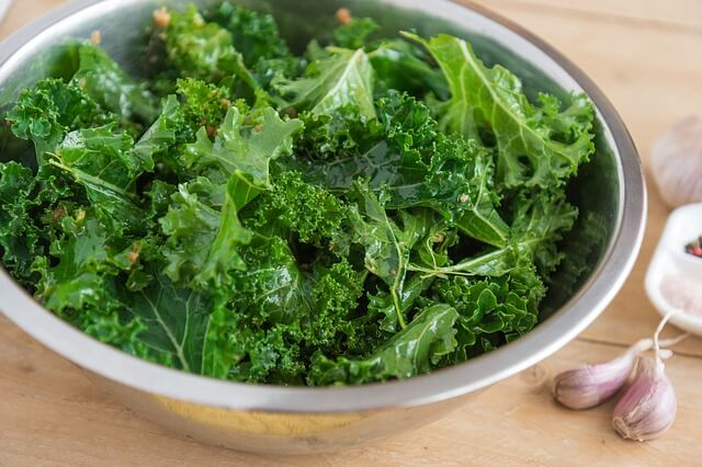 fresh kale leaves in a metal salad bowl