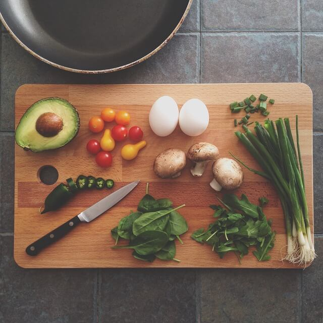 vegetables on a wooden cutting board ready for healthy holidays meal prep