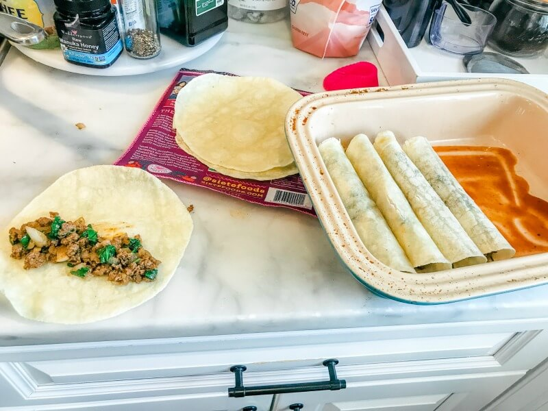 gluten-free beef enchiladas being layered in a casserole dish with gluten-free enchiladas sauce