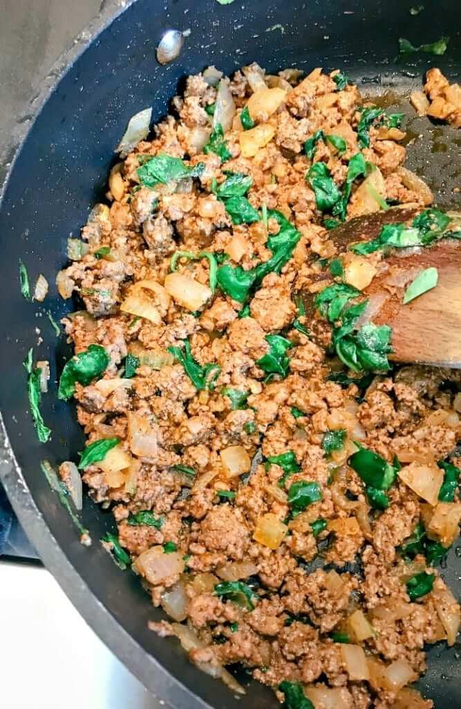 ground beef being stir-fried with spinach for making gluten-free enchiladas
