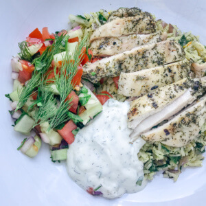 overhead shot of a healthy Greek marinated chicken and rice bowl with tzatziki