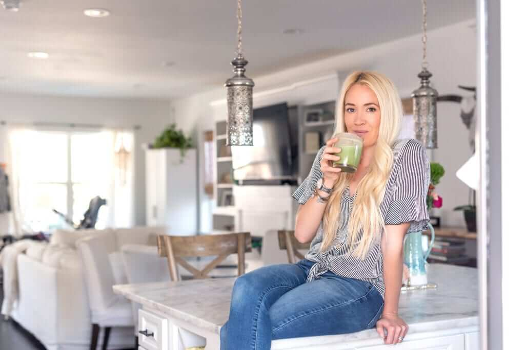 a woman sitting on a kitchen counter sipping a green collagen smoothie