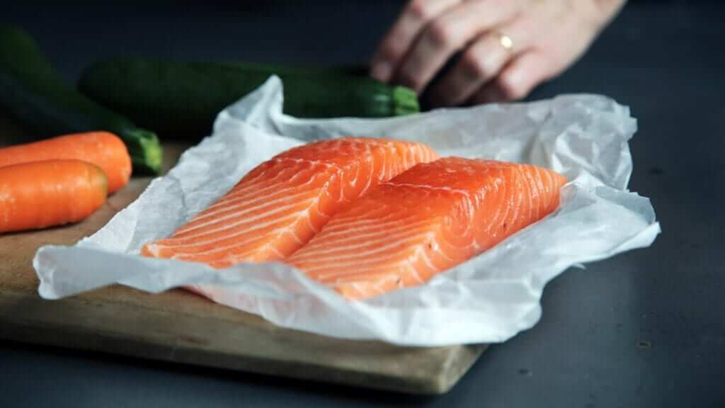 two fresh salmon fillets on a piece of parchment paper