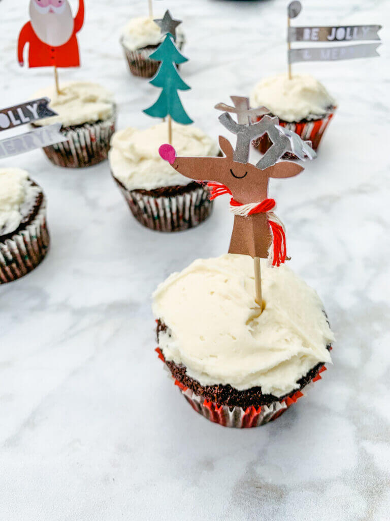 gluten-free chocolate peppermint cupcakes decorated with festive Christmas cupcake toppers on a marble countertop