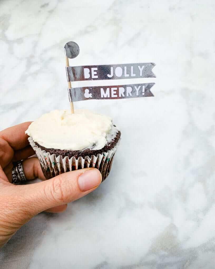 a hand holding a healthy gluten-free chocolate peppermint cupcake decorated with a Christmas cupcake topper