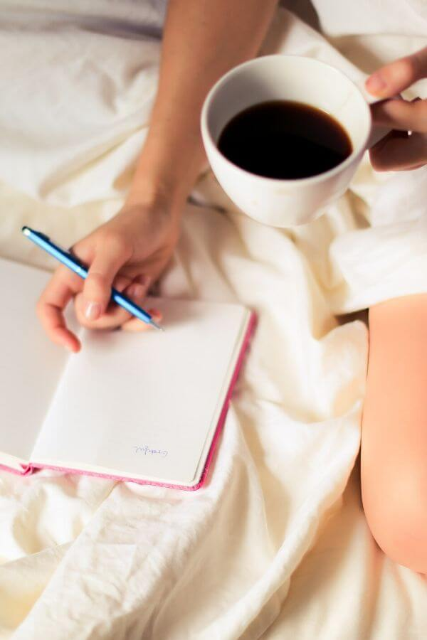 a woman writing a to-do list in bed with a cup of coffee in hand