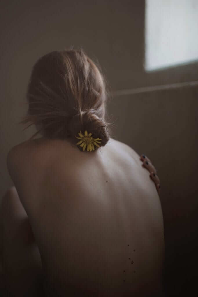 a woman with a flower in her hair sitting with her back towards the camera hugging her naked breasts to hide them from sight