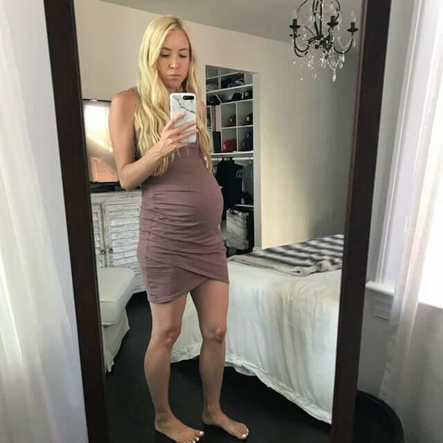 a pregnant blond woman taking a picture of herself in front of a whole body mirror