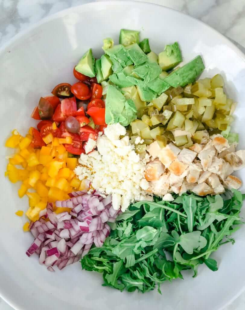 overhead shot of a healthy lunch salad packed with lean chicken,  arugula, peppers, cheese and avocado