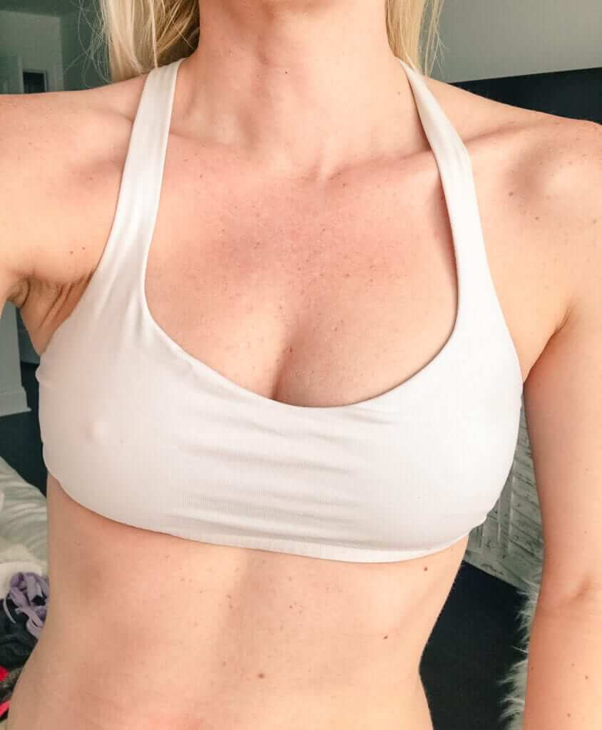 a woman in a sports bra showing her post-surgery cleavage after breast transfer procedure